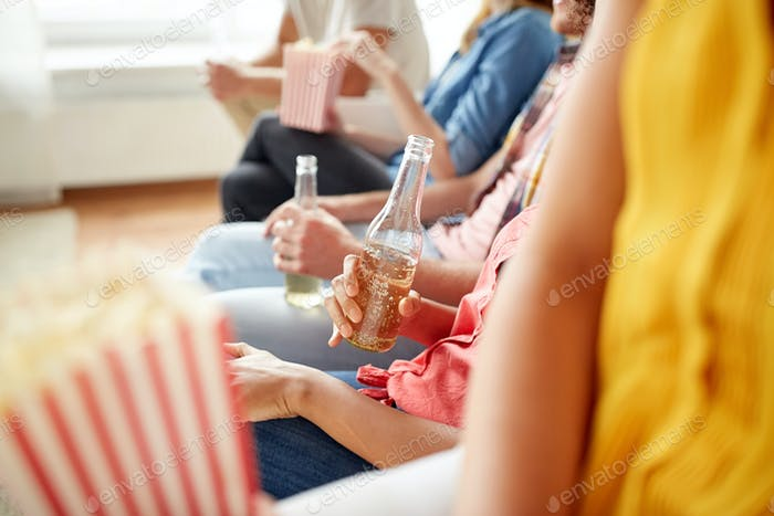 close up of friends with popcorn and beer at home