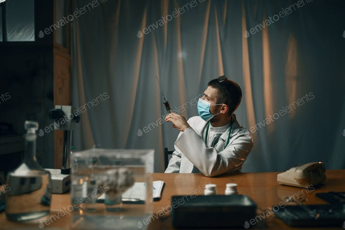 Psychiatrist in mask holding syringe with sedative