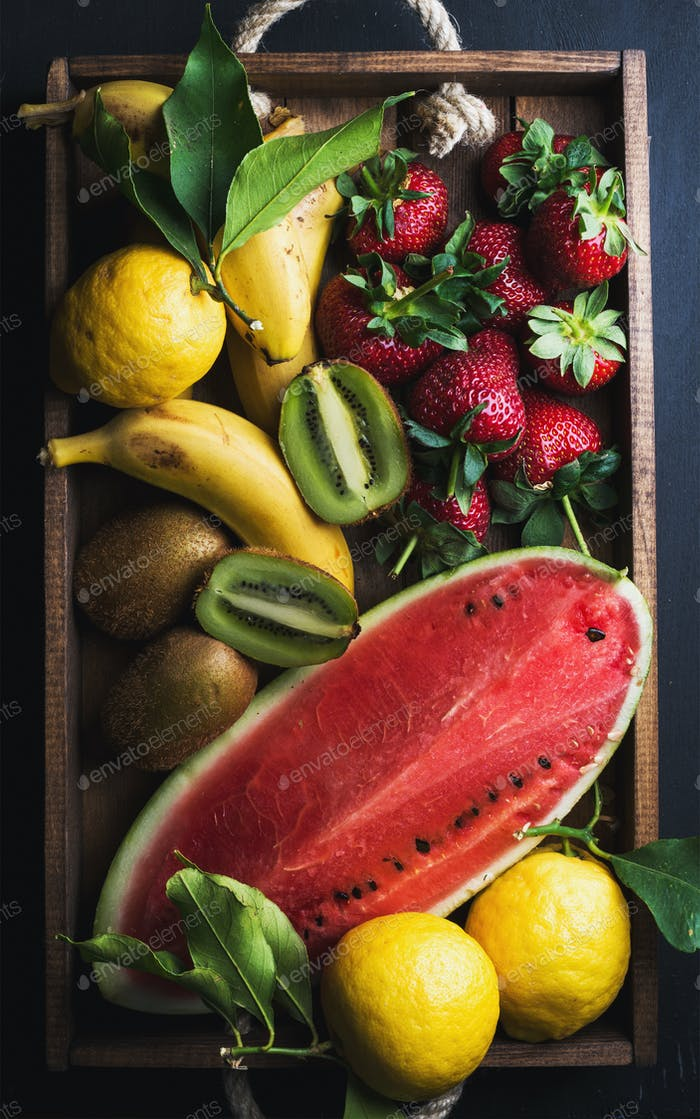 Various colorful tropical fruit selection in wooden tray over dark background