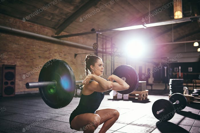 Starke Frau pumpt schwere Langhantel im Fitnessstudio