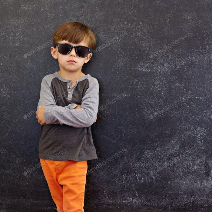 Smart little boy standing against blackboard