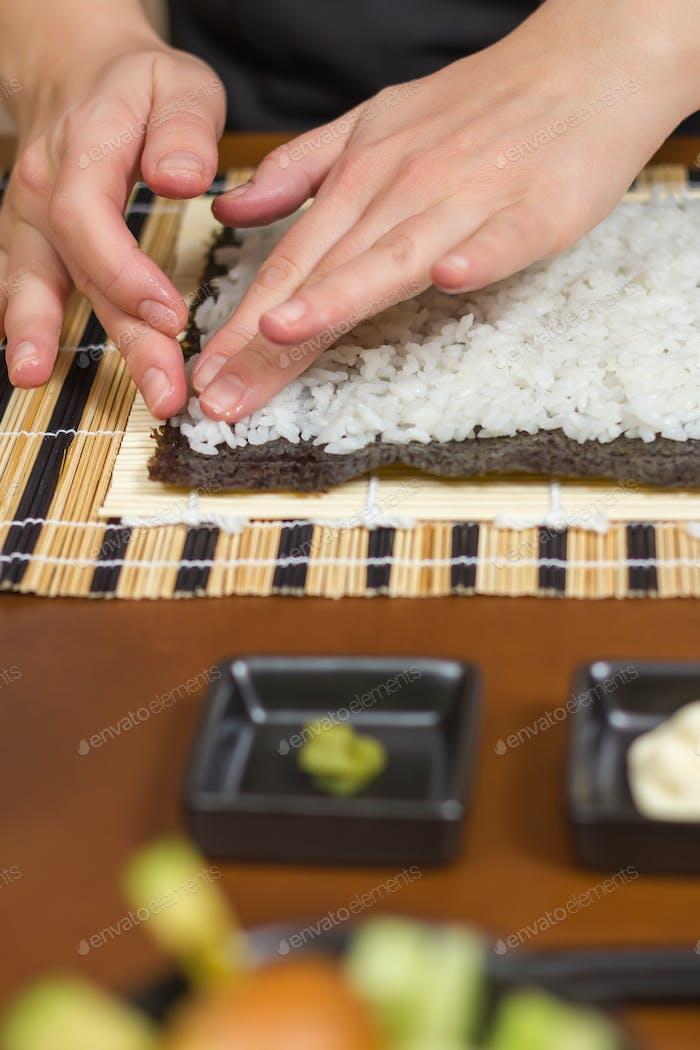 Frauenköchin füllt japanische Sushi-Rollen mit Reis