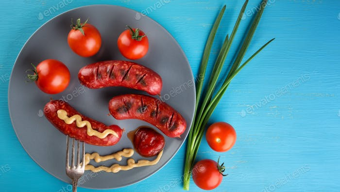 Nutritional sausages strung on fork with red tomatoes on plate