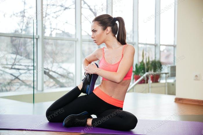 Sportswoman sitting on yoga mat and stretching legs