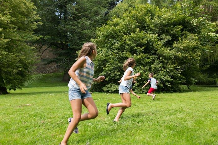 Gruppe von glücklichen Kindern oder Freunden spielen im Freien