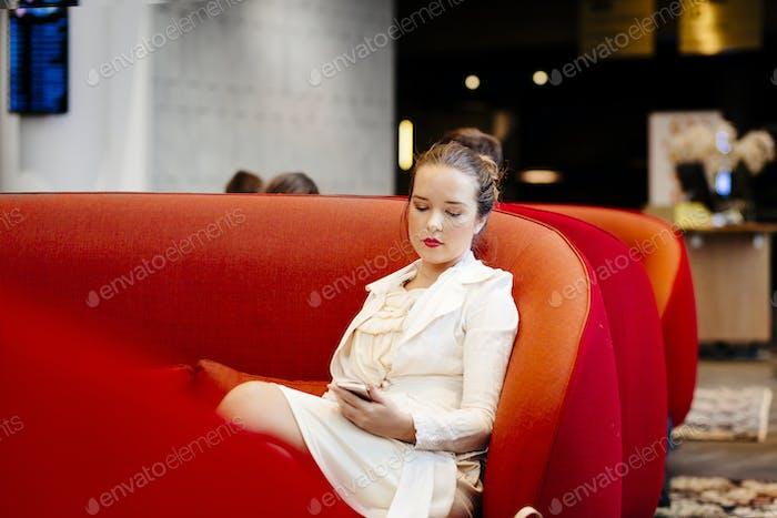 Geschäftsfrau hält Smartphone beim Sitzen auf dem roten Sofa im Hotel