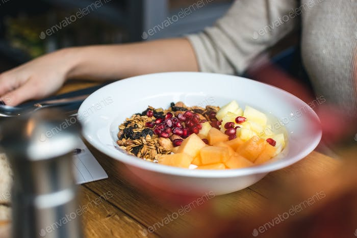 Eating granola with fresh fruits at restaurant