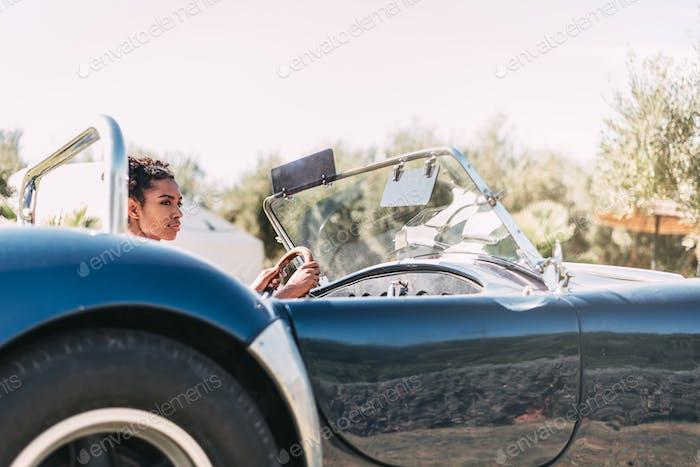 Schwarze Frau fahren ein Vintage-Cabrio Auto