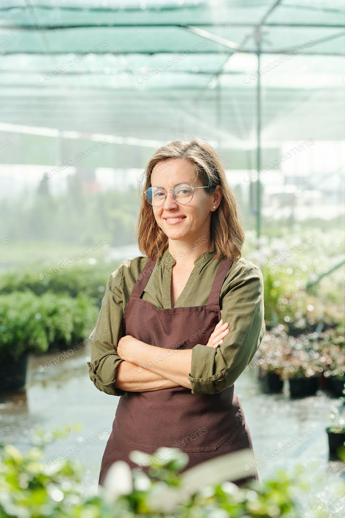 Happy mature female gardener in eyeglasses and apron standing among green plants and seedlings