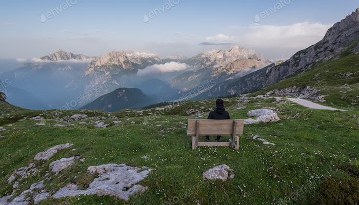 Male hiker enjoying the grand views of the mountains on the bench