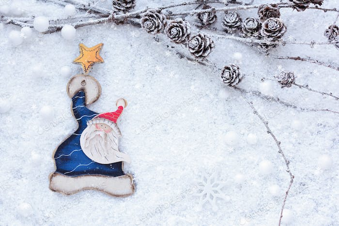 Larch branches with cones and Santa Claus on the snow. Christmas