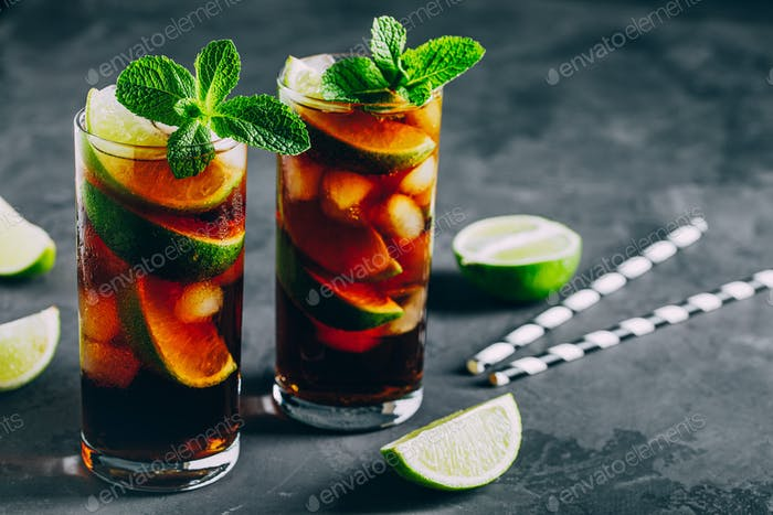 Rum and Cola Cuba Libre ice cold drink cocktail with lime and mint
