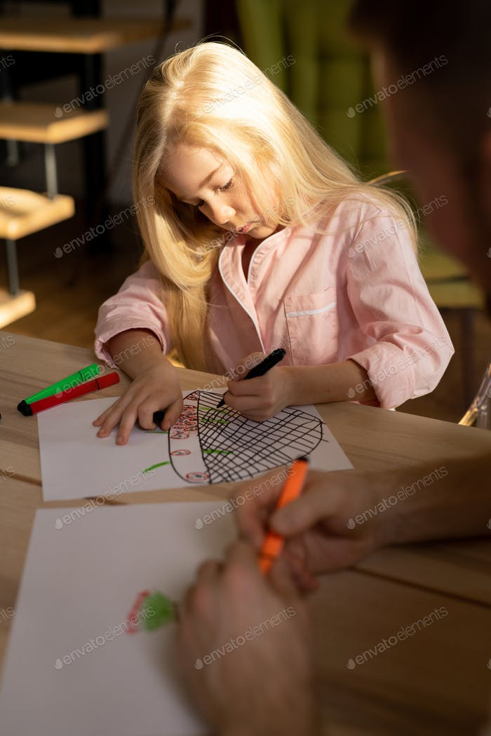 Cute little girl sitting by table while drawing picture with color highlighters