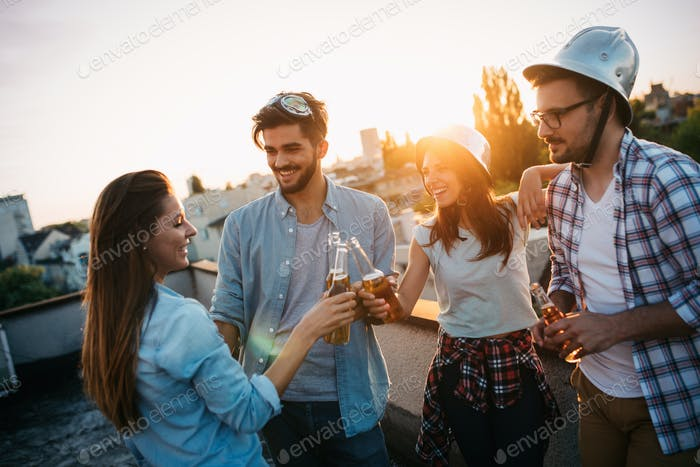 Junge Leute feiern auf der Terrasse mit Getränken bei Sonnenuntergang