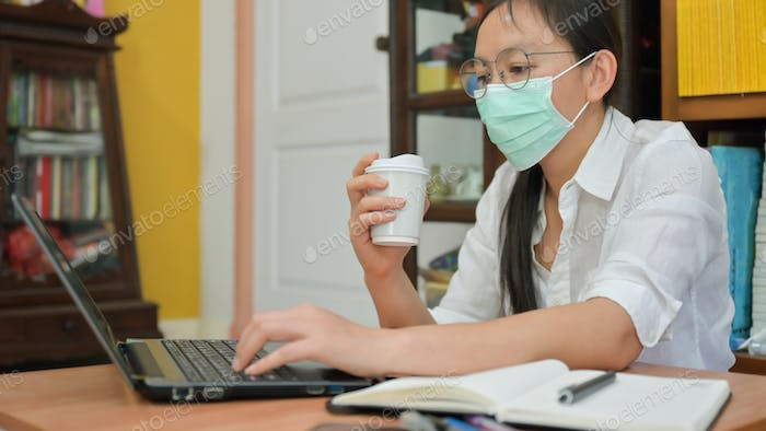 Asian woman mask holding a coffee cup and using a laptop,She works at home.