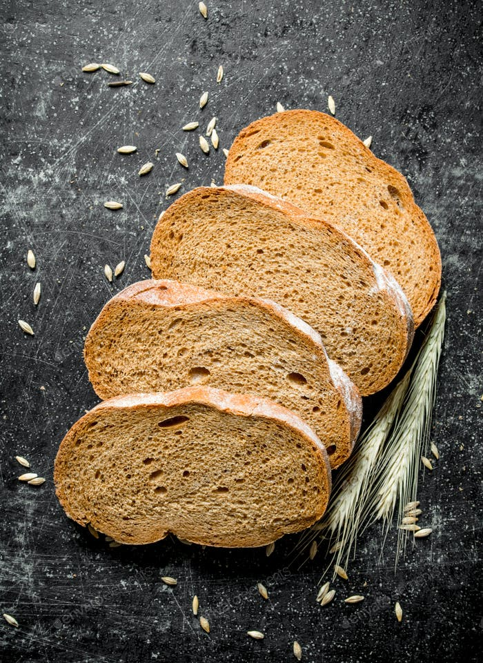 Pieces of fresh rye bread with grains and spikelets.