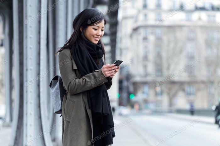 Lächelnde asiatische junge Frau mit ihrem Handy auf der Straße.