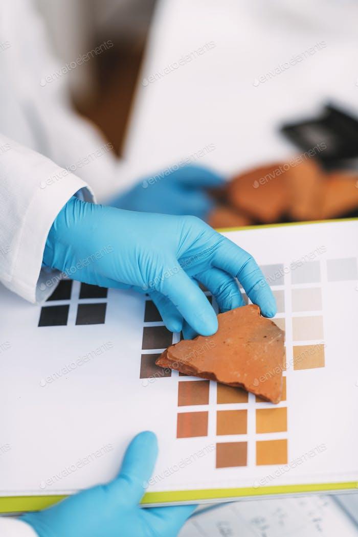 Archäologe vergleicht Keramik Farbe