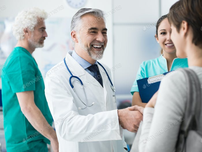 Confident doctor shaking patient's hand