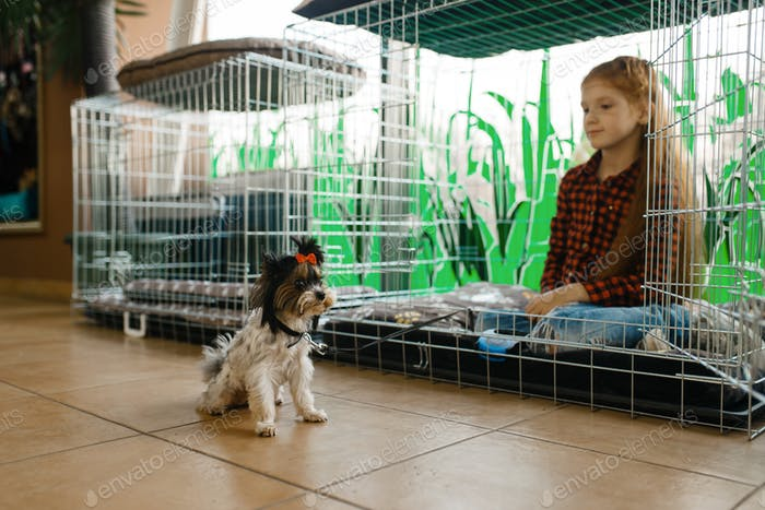 Little girl sitting in big cage, pet store