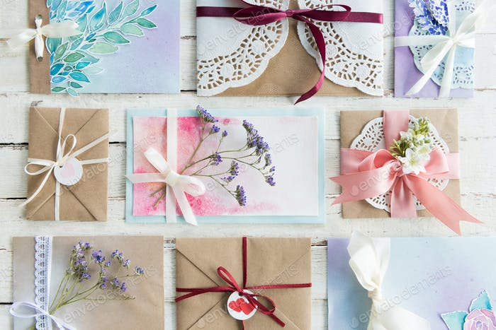 Draufsicht Sammlung von Umschlägen oder Einladungen auf weißer Holzplatte, Hochzeits-Einladungskarte
