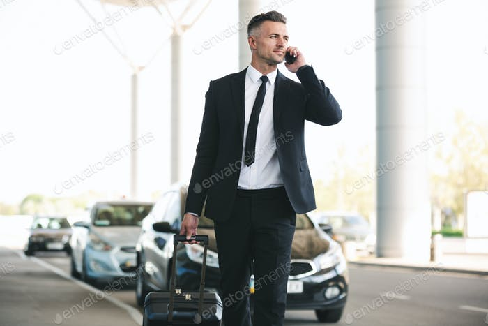 Confident mature businessman talking on mobile phone