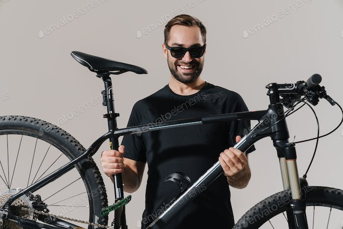 Happy young rider man smiling while posing with his bicycle