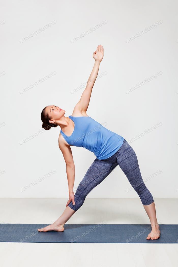 Woman doing yoga asana utthita trikonasana