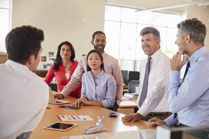 Business team meeting in an open plan office, close up