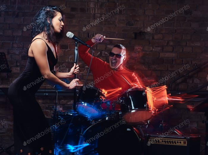 Jazz band performance. Couple of musicians - a drummer and a singer in a nightclub.