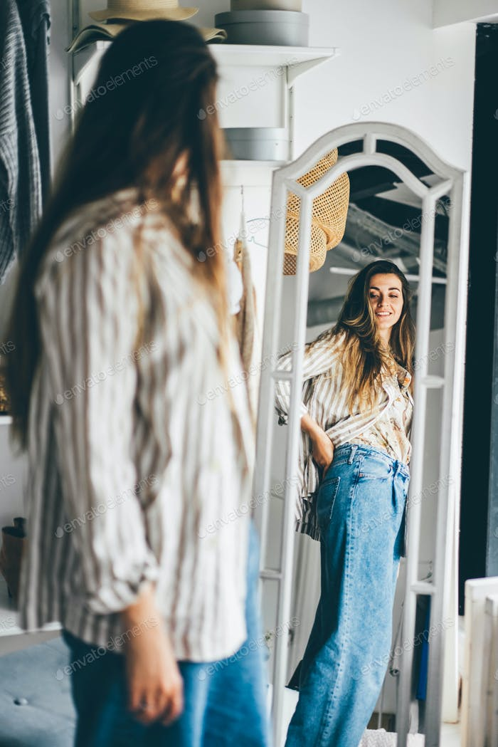 brunette woman standing near mirror with cheerful smile