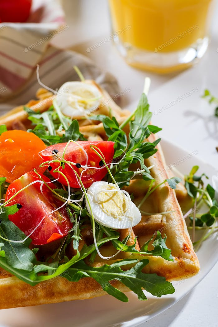 Fresh baked sweet belgian waffles with eggs, tomatoes, micro green and avocado served on a plate
