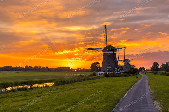 Molinos de viento de madera en una fila en la puesta de sol naranja
