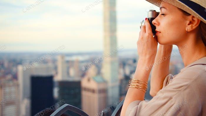 chica joven con un retro cámara en el techo