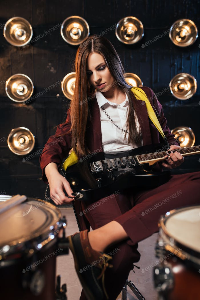 Female rock guitarist sitting behind the drum kit