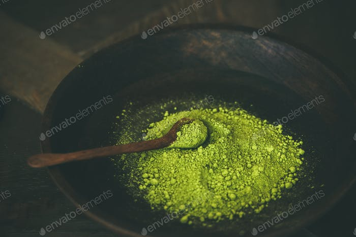 Japanese Matcha green tea powder in bowl with wooden spoon