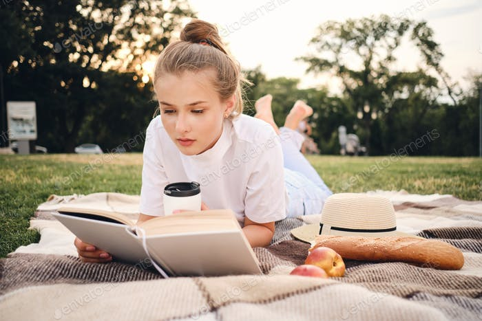 Young beautiful pensive woman lying on plaid thoughtfully reading book on picnic in city park