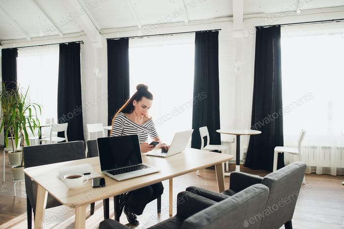 Attractive woman freelancer is working at a wooden desk on both laptop and smartphone while waiting