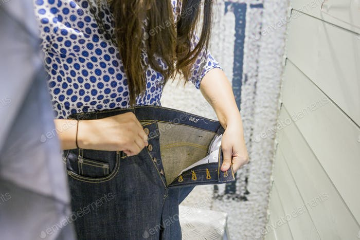 Woman trying jeans in changing room at factory