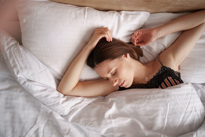 Attractive young woman sleeping well in bed