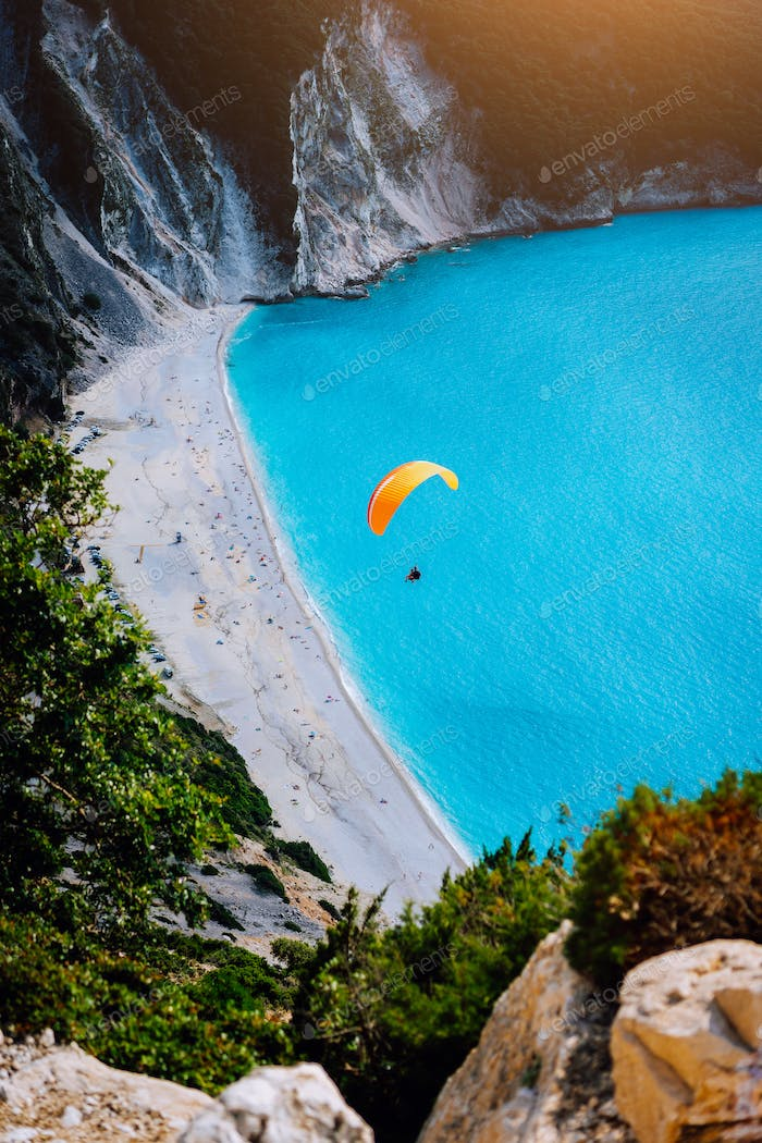 Myrtos Beach, Kefalonia Island, Greece. Figure of a parachutist skydiver with orange parachute