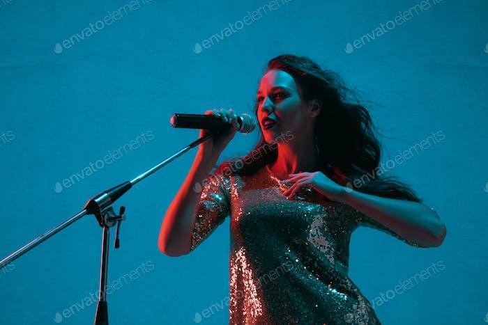 Caucasian female singer portrait isolated on blue studio background in neon light