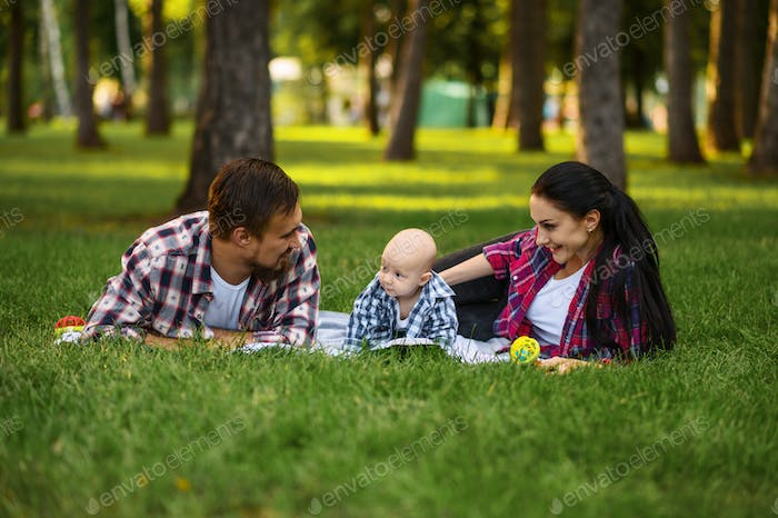 Mother, father and little baby leisures in park