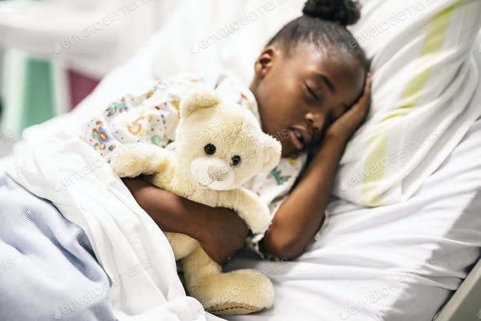 Little girl sleeping in a hospital bed