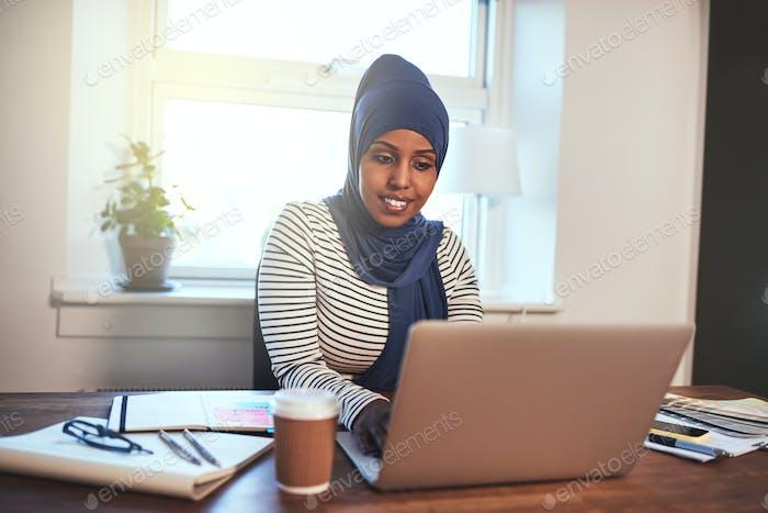 Smiling Arabic female entrepreneur working in her home office
