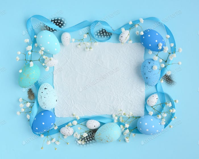 Easter eggs on a blue background. View from above, a piece of pa