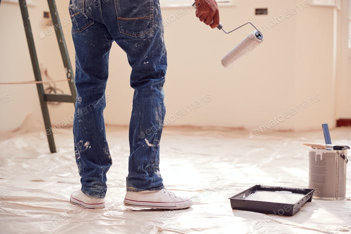 Close Up Of Man With Paint Roller Decorating New Home