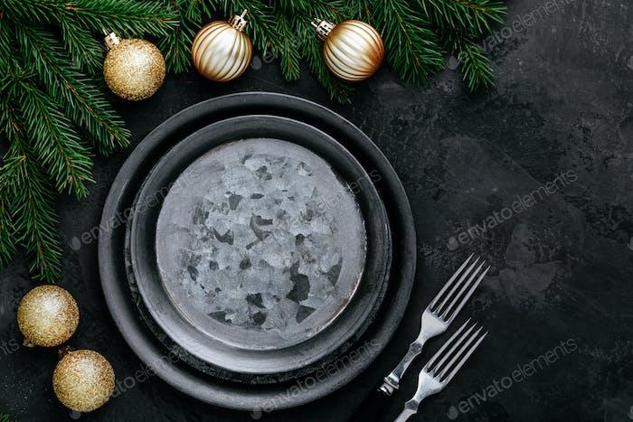 Fondo de la cena de Navidad con plato vacío y decoración dorada sobre mesa oscura.