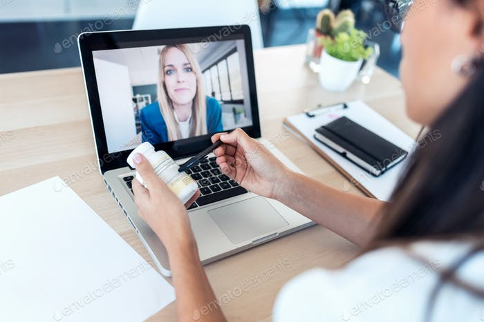 back view of a doctor attending to a woman patient and prescribing medicine through a video call