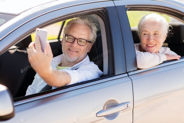 senior couple in car taking smartphone selfie